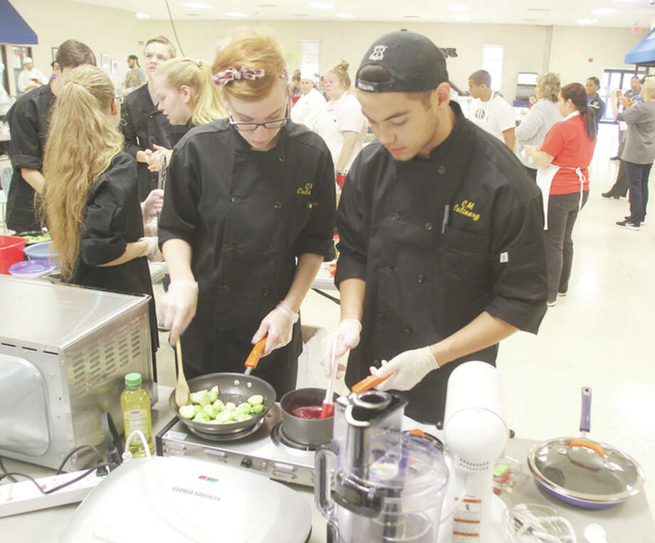 Sydney Fowler, left, and Steven Davis, students at Civic Memorial High School, work on dishes during the Platinum Chef competition Wednesday at the Southwestern Illinois College Sam Wolf Granite City Campus. The competition, the first in Madison County, pitted culinary teams from six local high schools against each other.