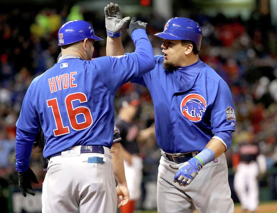 The Cubs' Kyle Schwarber is congratulated by first base coach Brandon Hyde after hitting an RBI single during the fifth inning of Game 2 of the World Series Wednesday night in Cleveland. Photo: AP