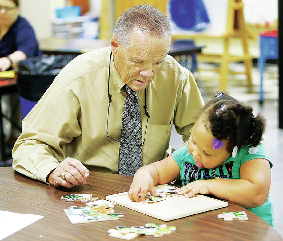 Ss. Peter & Paul Catholic School Principal Harry Cavanaugh lends a hand Thursday in the pre-school classroom at the Alton school. Cavanaugh recently received the Distinguished Educator Award from Eastern Illinois University.