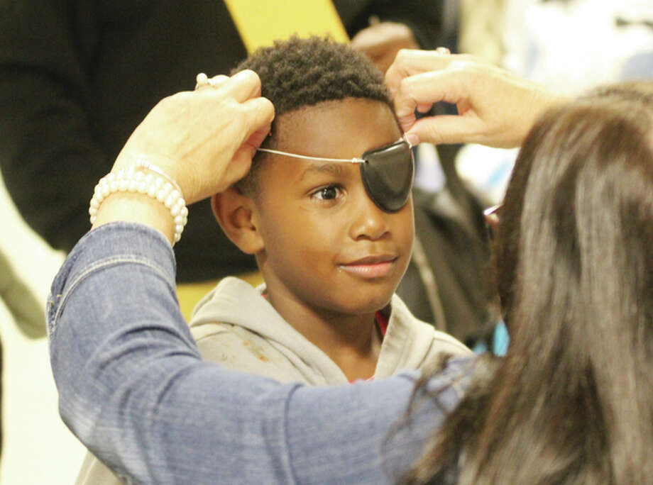 Eimaj Murrell, 7, gets an eye-patch from Teresa Arview at the East Elementary School family reading night and book fair Thursday. The evening had a pirate theme and included a treasure hunt, pirate play written by one of the teachers, and a pirate ship, the Gypsy Rose.