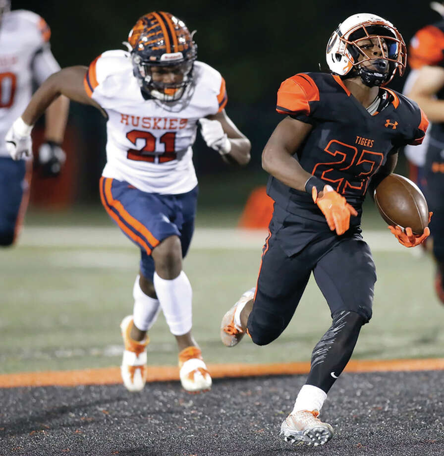 Edwardsville's Dionte Rodgers (right) breaks into the secondary and outruns Oak Park-River Forest's Brenden Flowers for a 55-yard touchdown run in the first quarter Friday night at the District 7 Sports Complex in Edwardsville. Rodgers finished with 246 rushing yards and two TDs. Photo: Scott Kane / For The Telegraph