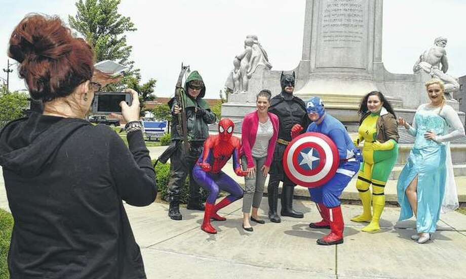 Dakotah Ehle (left) takes a photo of her friend Rebyka Watson as she poses with members of the Superheroes Saving Smiles Wednesday in Jacksonville's Central Park. Photo: Samantha McDaniel-Ogletree | Journal-Courier
