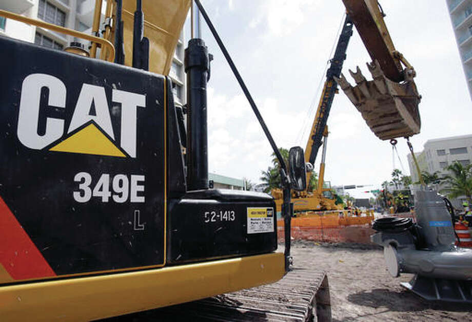 In this Wednesday, Sept. 17, 2014, file photo, a Caterpillar 349E Hydraulic Excavator operates on a construction site in Miami Beach, Fla. Caterpillar reports financial results Tuesday, Oct. 25, 2016. (AP Photo/Wilfredo Lee, File)