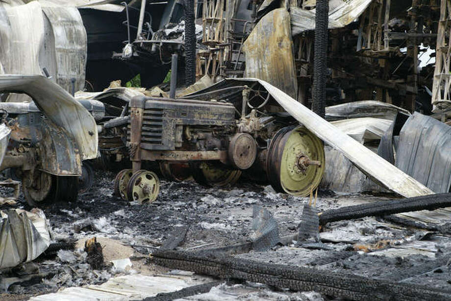 The shell of a tractor sits among the ashes and ruins Thursday, a day after fire destroyed an Alexander machine shed and caused more than $1 million damage.