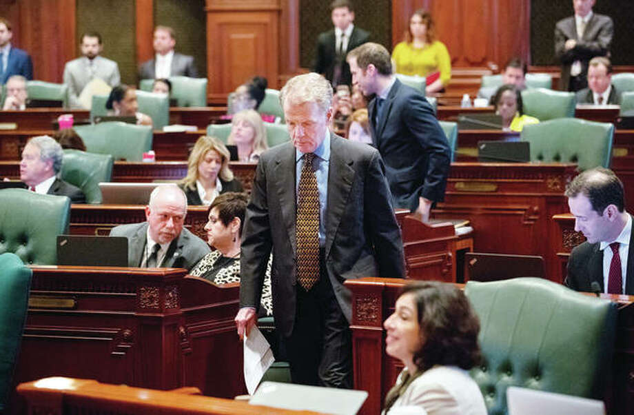 House Speaker Michael Madigan leaves the House floor following a vote to adopt a spending bill amendment in Springfield on Friday. Madigan said he will contact the bond rating agencies to ask them to postpone any decisions on further rate reductions while the General Assembly finalizes work on its first full budget in three years.