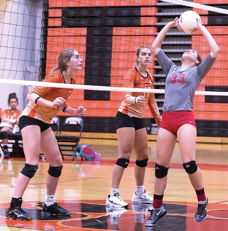 Edwardsville's Kate Martin (left) and Rachel Pranger (middle) watch at the net while Alton's Sydney Schmidt sets for a teammate during a Southwestern Conference match Oct. 13 in Edwardsville. The Tigers, coming off SWC and regional championships, open play in the Chatham Glenwood Class 4A Sectional on Tuesday night against SWC rival O'Fallon (31-6) at Belleville West. The Tigers defeated the Panthers twice during the regular season. Regional champs throughout Illinois compete in sectional semifinals Tuesday. At the Vandalia Class 2A Sectional, Carlinville (22-13) meets Shelbyville (28-9). At the Jacksonville Routt Class 1A Sectional, Calhoun (28-4) plays Springfield Lutheran (24-11) in the first semi before Mount Olive (25-5) takes on New Berlin (24-11). At the Lebanon Class 1A Sectional, Metro East Lutheran (11-22-1) plays Clay City (28-1). Sectional championship matches will be played Thursday night. Photo: Scott Kane / For The Telegraph