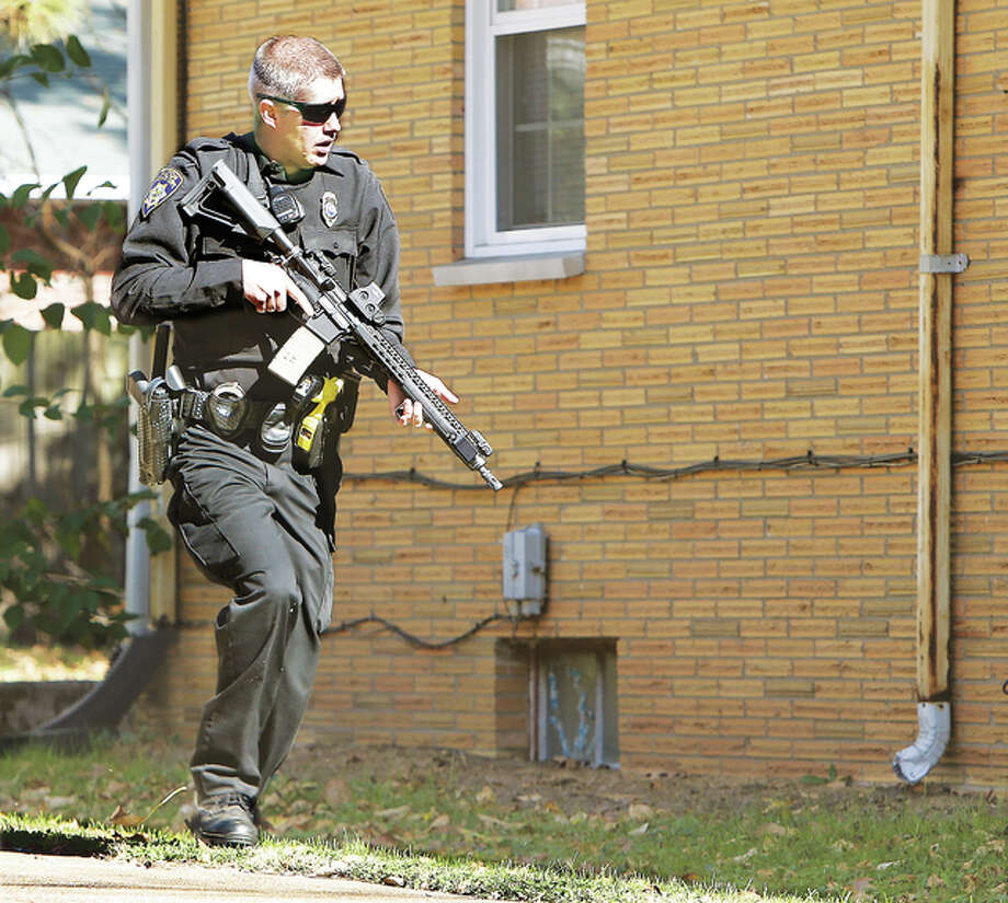 A heavily armed Alton police officer races up to the house in the 300 block of Lindenwood in Alton where a man allegedly forced entry and made the female occupant lie down on the floor at gunpoint. The man, who was wearing a surgical mask, started looking through the house, giving the occupant time to flee for safety. She ran to Eunice Smith School. Alton officers searched the house and started a canine-track, which turned up a surgical mask in a backyard in the 400 block of Brentwood, not far away. The man remained at large Tuesday afternoon.