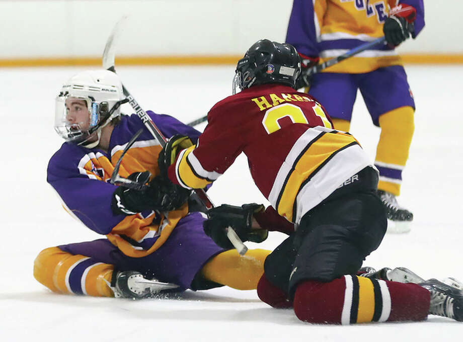 Bethalto's Anthony Russo, left, hits the ice and collides with East Alton-Wood River's Kaleb Harrop during Tuesday night's MVCHA game at East Alton Ice Arena. Photo: Billy Hurst | For The Telegraph