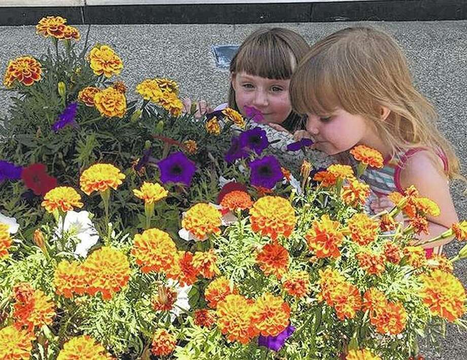 Naomi and Natalie Brown stop to smell the flowers during a trip to downtown Jacksonville.