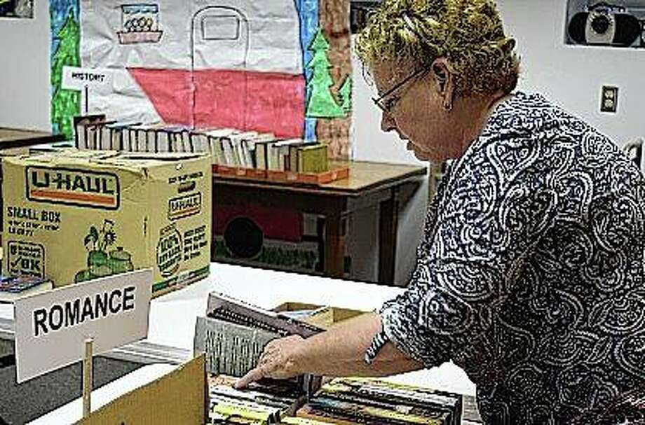Mary Lou Lael, the president of the Friends of the Library board, sets up for the boards book sale Friday. The book sale will take place from 10 a.m. to 4 p.m. today in the lower level of the Jacksonville Public Library. Photo: Samantha McDaniel-Ogletree | Journal-Courier