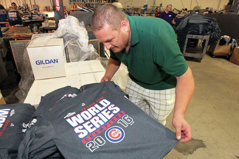 Owner Larry Hanneke inspects one of the nearly 40,oo0 Chicago Cubs championship T-shirts his company is making at Hannekes Logo Wear in St. Louis. The shirts are being shipped to stores in the Chiccago area. The Cubs defeated the Cleveland Indians Wednesday to win the World Series. Photo: Bill Greenblatt | UPI