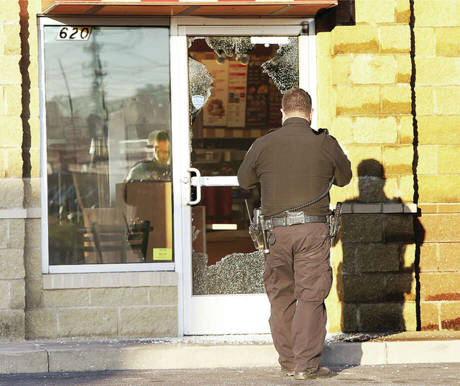 Alton police officer Manuel Espinoza photographs the broken glass door on the east side of the downtown Alton KFC/Taco Bell, 620 Landmarks Blvd., early Friday morning following an overnight burglary of the restaurant. The burglar, or burglars, broke the glass door with a brick and stole three cash boxes from the restaurant according to police. Espinoza spent most of his time photographing and fingerprinting the area behind the counter Friday morning.