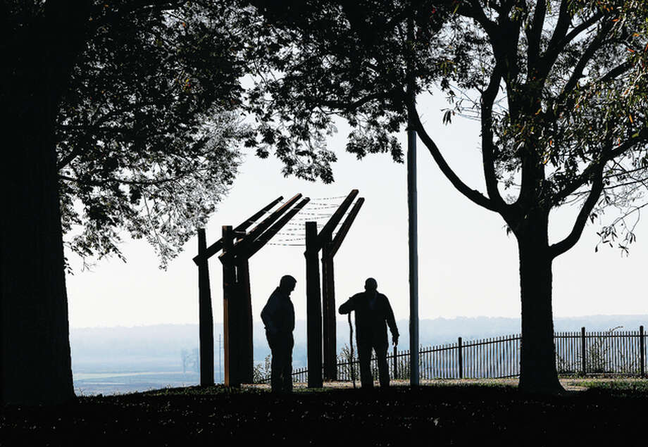 Two men are silhouetted Friday near the overlook of Alton's Riverview Park, which provides an unparalleled view of the Mississippi River from the bluff-top. The state of Illinois has released the promised funds from the state Open Space Lands Acquisition and Development Grant program which will allow for the completion of planned improvements in one of the city's oldest and most historic parks.