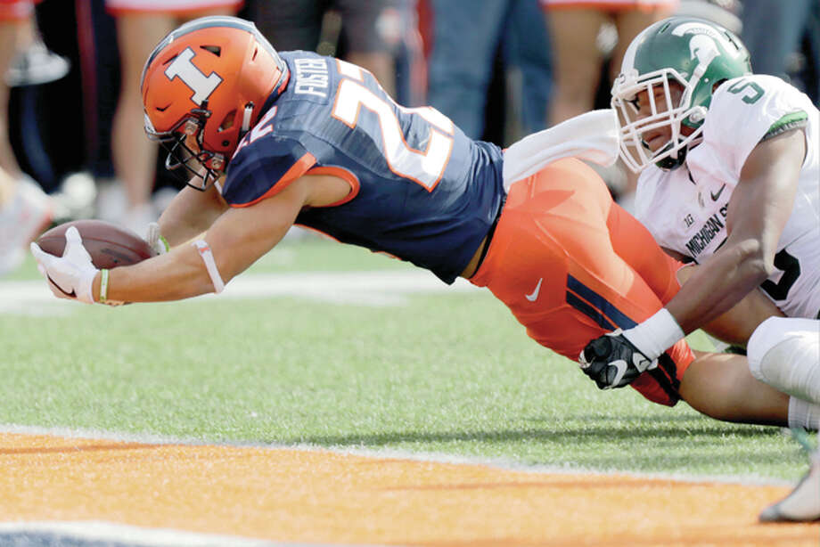 Illinois running back Kendrick Foster (22) stretches the ball across the goal line for a touchdown against Michigan State linebacker Andrew Dowell (5) Saturday in Champaign. Photo: AP