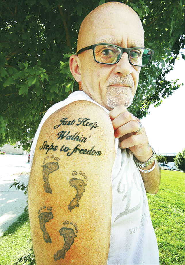 "Jack Wilcox, 60, lost his son to a heroin overdose in November. He has since started a support group for others who have lost a loved one to substance abuse, and is now planning on walking to the capitol building in Springfield to raise awareness. Wilcox poses here with his tattoo, reading ""Just Keep Walkin', Steps to freedom,"" the same name as his support group."