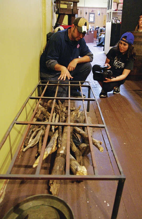 Student documentary producers Javier Navarrete and Rebecca Paradis discuss an exhibit Sunday to be included in their film project, which will feature predominantly the Historic Museum of Torture Devices. Photo: David Blanchette|For The Telegraph