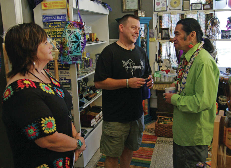 Donna and Dave Nunnally, owners of It's Raining Zen, talk in their shop with Johnny Moses before a Native American program Moses gave in Mineral Springs Mall Sunday. Photo: David Blanchette|For The Telegraph