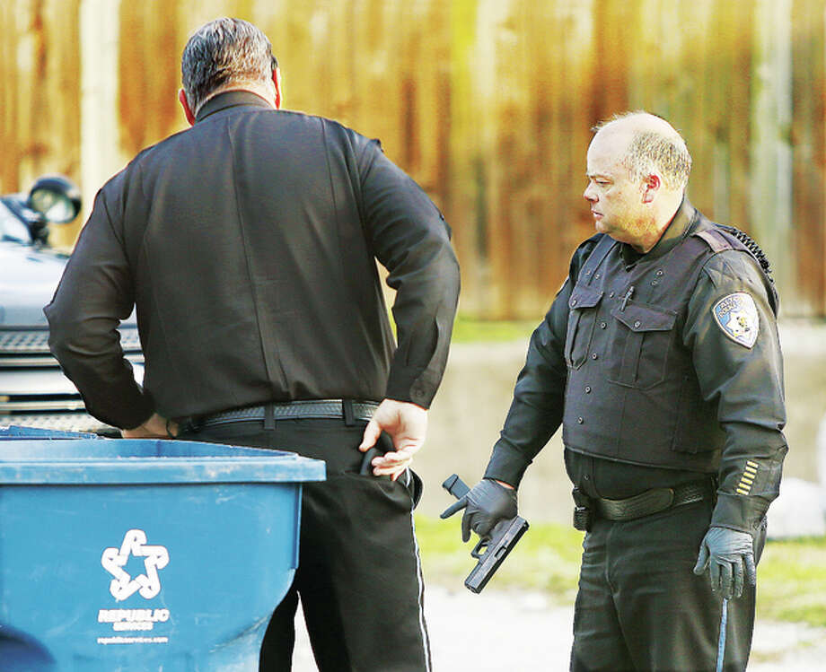 "Alton Police Chief Jason ""Jake"" Simmons, right, and Sgt. Terry Buhs, left, stand by trash cans in the rear of a building in the 500 block of Ridge Street Monday afternoon after recovering a handgun with an extended ammunition clip, being held by the chief. The gun is suspected of being the one used in a ""shots fired"" incident nearby, which launched a large police manhunt for the gunman including the use of a police dog. The search for the suspect came at a bad time with multiple school buses unloading small children throughout the search area. Nobody was reported as having been shot despite the gunfire. An officer heard the shots fired in the same area where only about 45 minutes earlier police had broken up a large fight that sent one man to Alton Memorial Hospital. Photo: John Badman