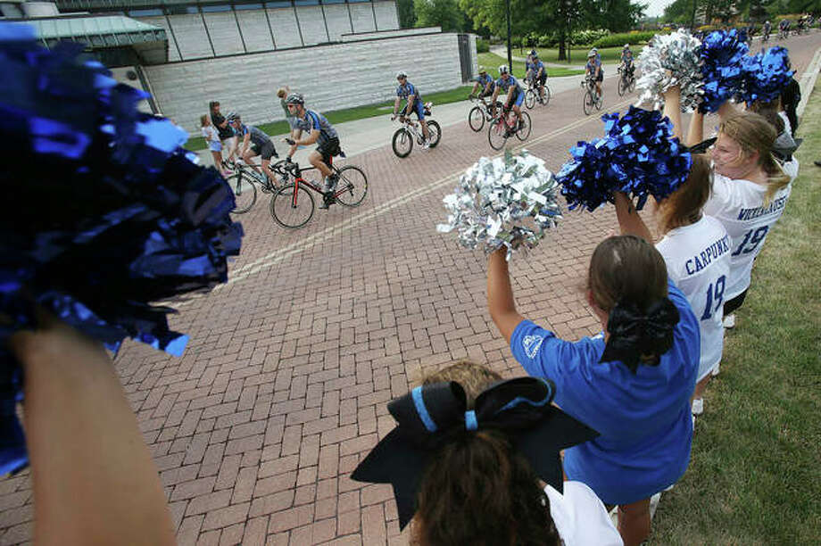 Cyclists participating in the 13th annual police charity Cycle Across Illinois pull into their first stop Thursday at Lewis and Clark Community College in Godfrey as cheerleaders from Marquette Catholic High School in Alton welcome them. The 300-mile bike ride, which started early Thursday at the Mississippi River in Alton and will end Sunday in Maywood, raises money for the survivors of fallen law enforcement officers. The group stopped at several locations along the way, including in Morgan County.