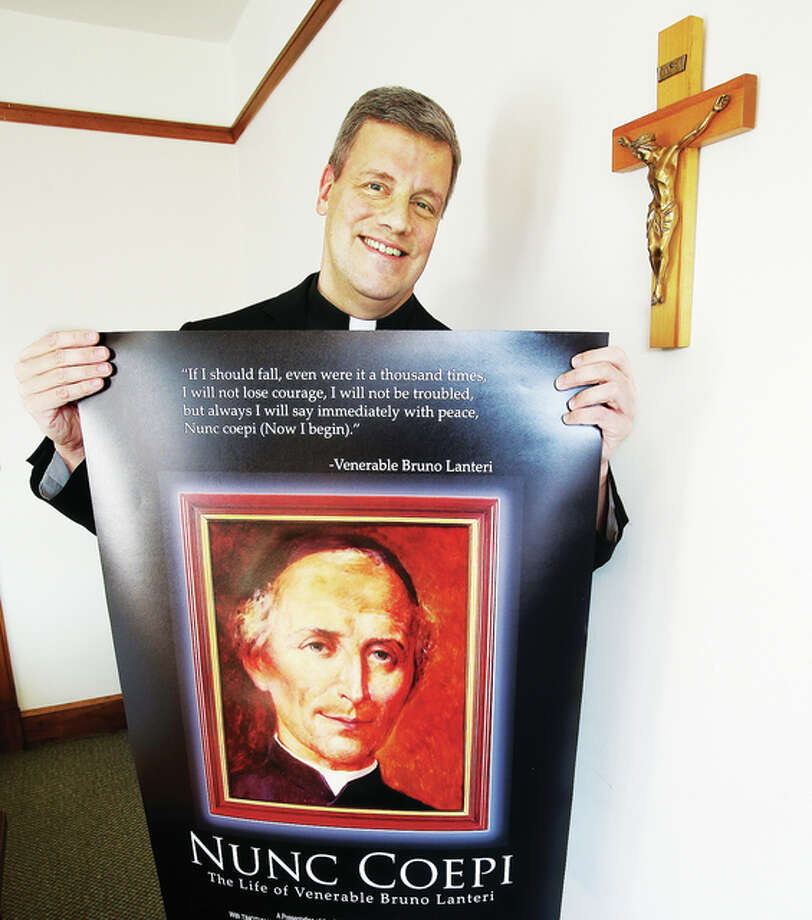 Fr. John Wykes, from St. Mary's Catholic Church in Alton, holds a promotional poster for the film he co-produced and directed on Bruno Lanteri, the founder of his order, Oblates of the Virgin Mary. The film will be previewed in Italy, Boston and Alton. Photo: John Badman|The Telegraph
