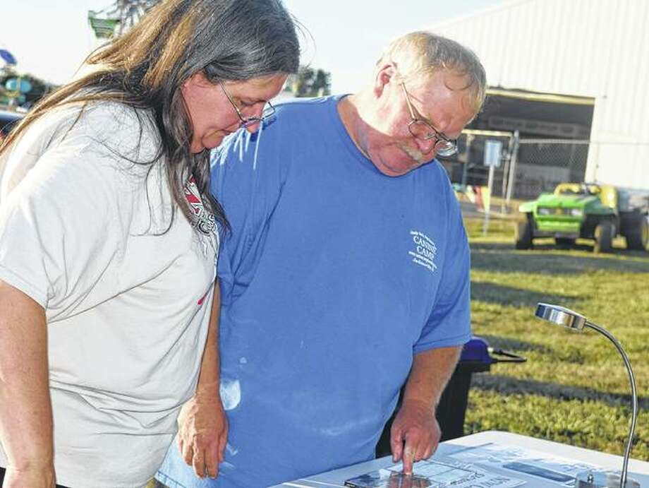 Debbie and Dave Harris of Jacksonville look at the Trace Adkins merchandise Friday during the Morgan County Fair. Photo: Samantha McDaniel-Ogletree   Journal-Courier