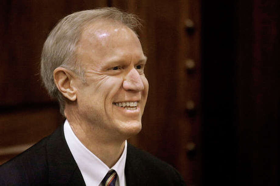 FILE - In this Jan. 27, 2016 file photo, Illinois Gov. Bruce Rauner is greeted by applauds from lawmakers before he delivers his State of the State address to a joint session of the General Assembly in the House chambers at the Illinois State Capitol in Springfield, Ill. Rauner and fellow Republicans eliminated the Democrats' supermajority in the Illinois House Tuesday to strengthen the governor's bid to implement a union-weakening, business-friendly agenda that Democrats have resisted for nearly two years. (AP Photo/Seth Perlman)