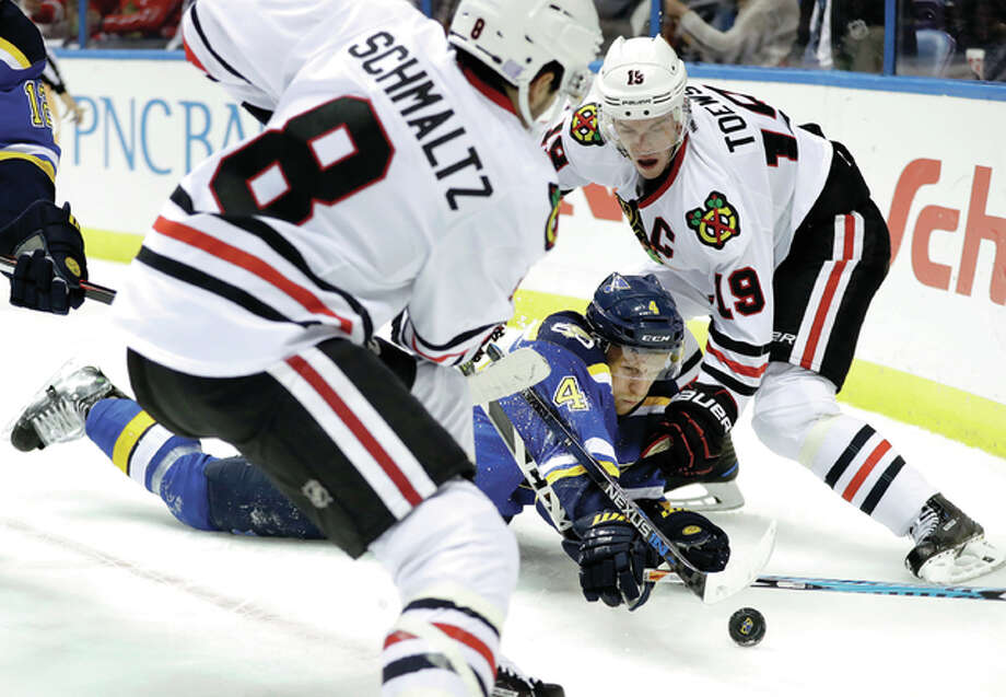 The Blues' Carl Gunnarsson reaches for the puck along with Chicago Blackhawks' Nick Schmaltz (8) and Jonathan Toews (19) Wednesday night in St. Louis. Photo: AP