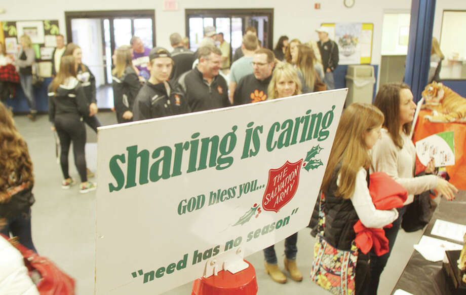 "People stand in line to buy tickets to the annual ""Clash of the Cats,"" a charity hockey game between the Edwardsville Tigers and the Oakville Tigers recently at the East Alton Ice Rink. Proceeds from the game benefit the Alton Salvation Army. The event also featured one of the bell-ringing campaigns kettles. The campaign will be kicking off in a few weeks."