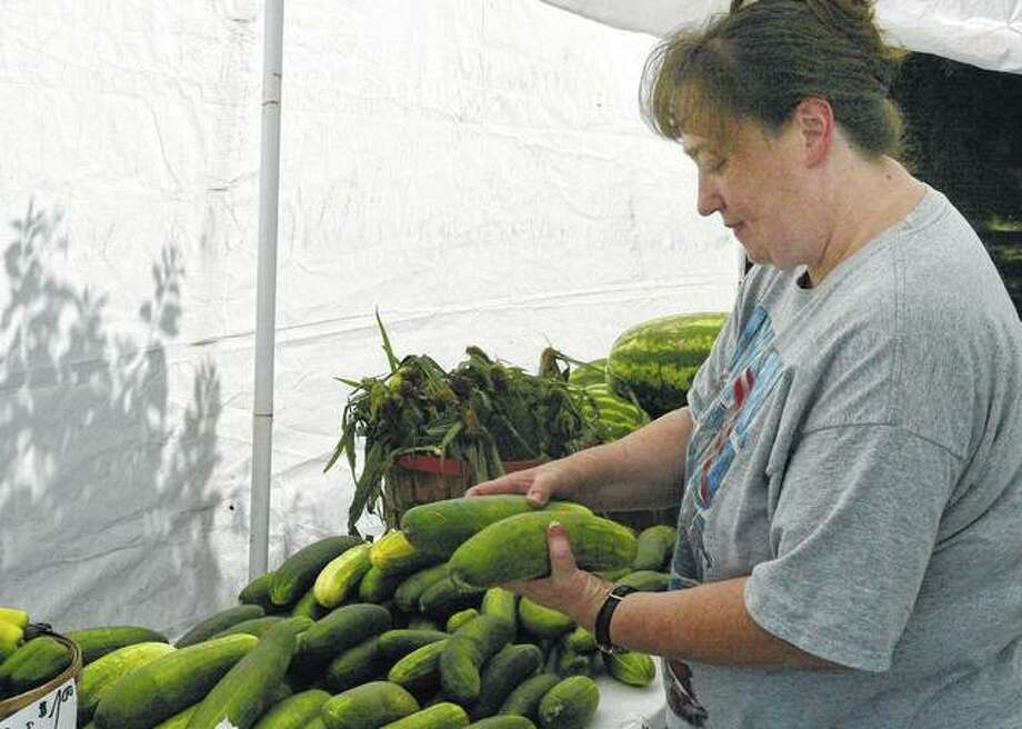 Denise Andrews of Virginia picks out cucumbers Tuesday at a JJ and Spears Produce stand on South Main Street. Photo: Samantha McDaniel-Ogletree | Journal-Courier