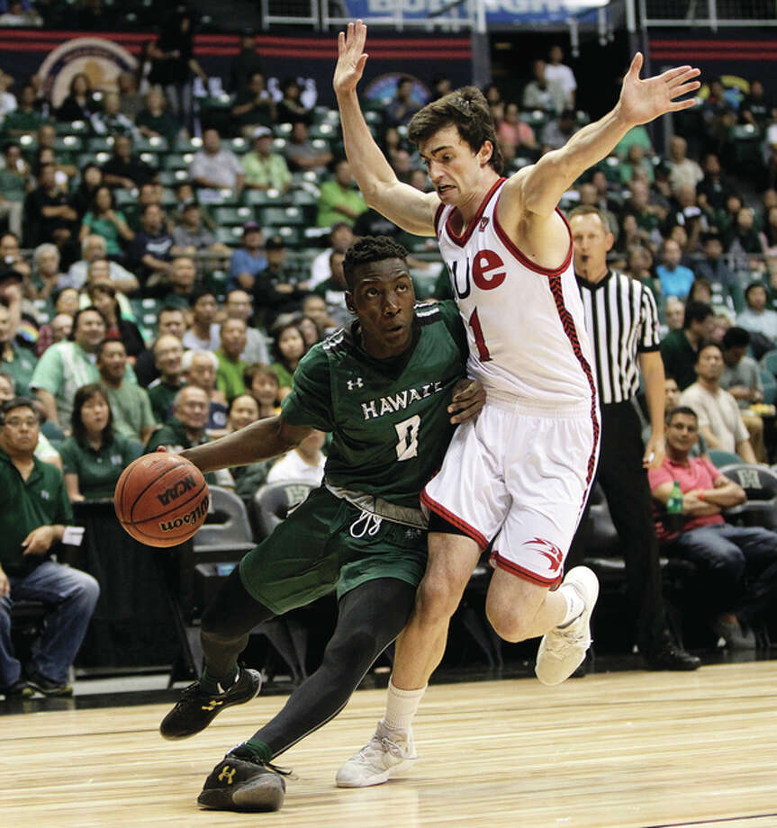 SIUE's Burak Eslik (right) defends as Hawaii's Leland Green drives against toward the basket during the first half of a Friday night's game in Honolulu. Photo: Associated Press