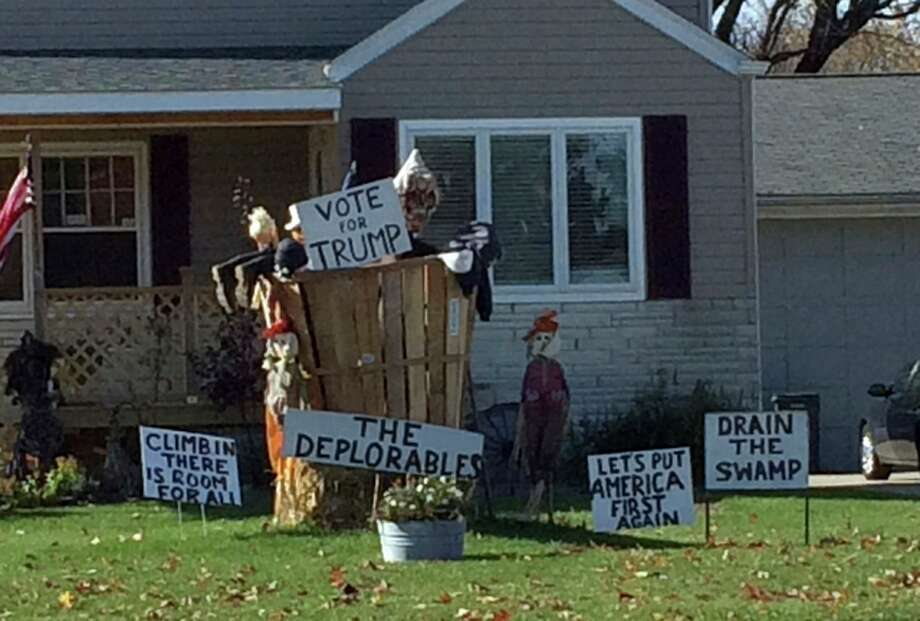 """In a photo from Nov. 11, a supporter of Donald Trump displays signs supporting the President-elect in St. Clair Shores, Mich. The front lawn features a large wooden basket with life-sized, scarecrow-like people sticking out and a sign labeling it """"The Deplorables,"""" a reference to Hillary Clinton's description of half of Trump's supporters as a """"basket of deplorables."""" The lawn display also features a sign that reads: """"Climb In There is Room For All."""" Photo: (AP Photo/Jeff Karoub)"""