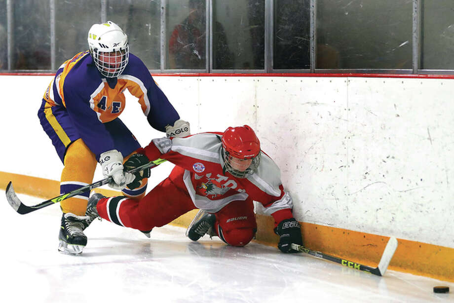 Bethalto's Jacoby Robinson, left, delivers a check to Alton's Connor Neely as they chase the puck along the boards in Monday night's MVCHA game at the East Alton Ice Arena. The Redbirds and the Eagles skated to a 3-3 tie. Photo: Billy Hurst | For The Telegraph