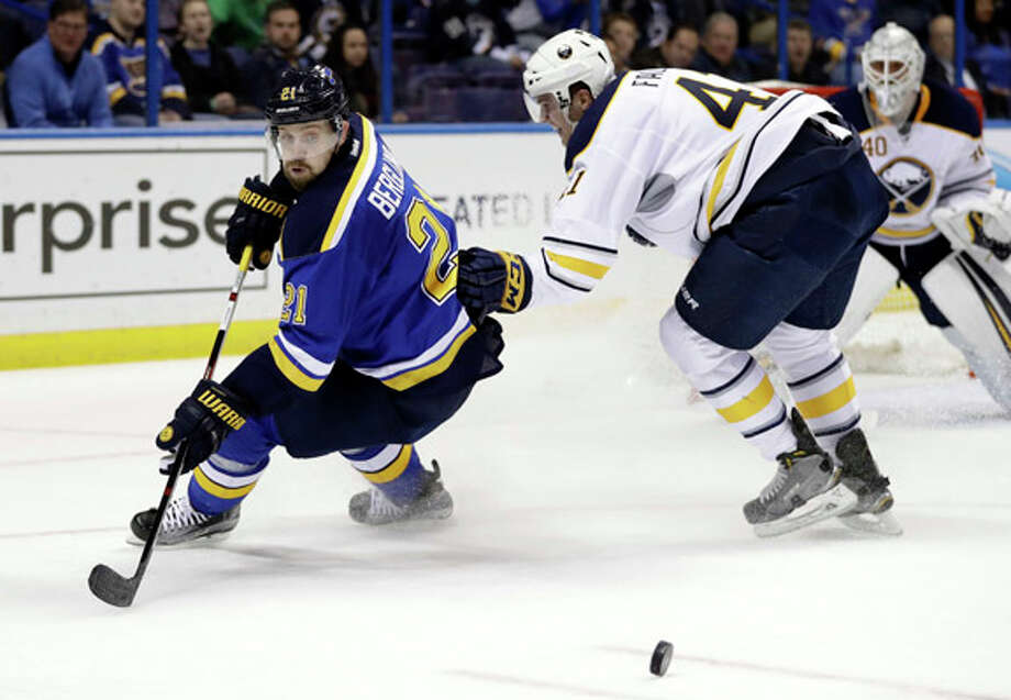 The Blues' Patrik Berglund (21) watches the puck as Buffalo's' Justin Falk skates past during the second period of Tuesday's game in St. Louis. Photo: Jeff Roberson | AP
