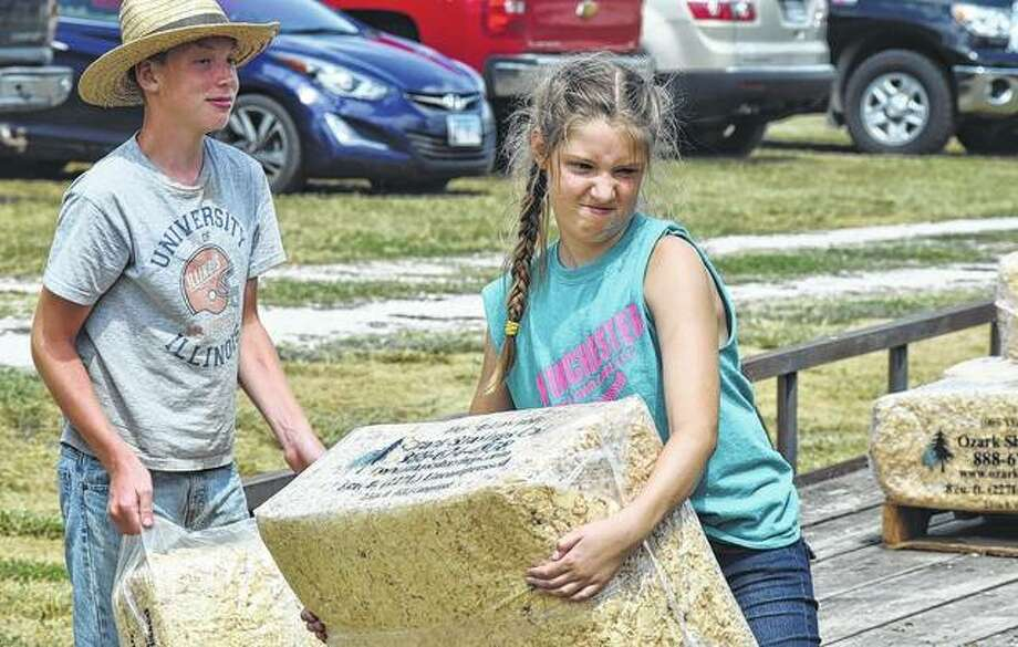 Scott County 4-H member Annabell Schafer (right), 12, gives a grimace of determination Monday as she and Wyatt Schafer, 13, throw bales of bedding during the Scott County 4-H Show Junior Fair weigh-in. The fair continues this week at the fairgrounds at 401 N. Walnut St. in Winchester.