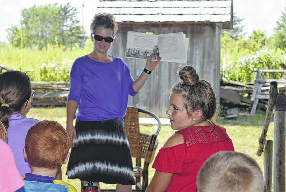 Virginia Library director Janet Horton (center) reads a book about attending school on the prairie Tuesday at the Rexroat Prairie cabins for the final summer story time. Photo: Samantha McDaniel-Ogletree | Journal-Courier