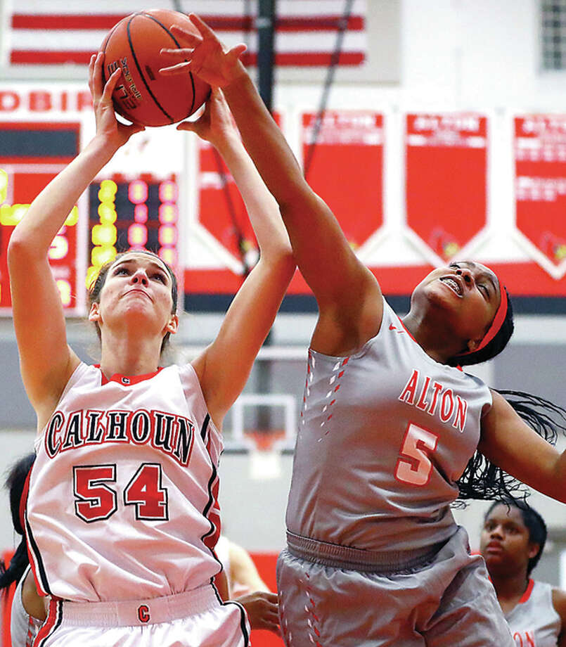 Calhoun's Grace Baalman, left, puts up a shot as Alton's Allurah Bowens attempts a block during Wednesday night's game played at Alton High. Photo: Billy Hurst | For The Telegraph