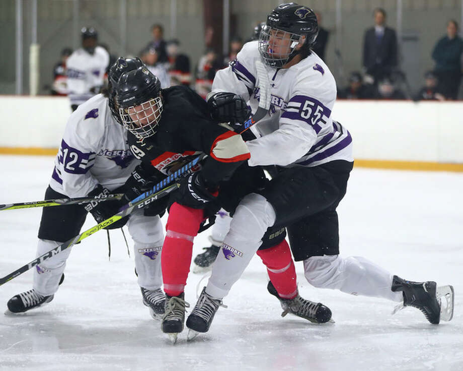 SIUE's Nick Faulkner, middle, battles for the puck with McKendree's Nick Gay, right, and Jason Beilke, Jr. action earlier this season at the East Alton Ice Arena. Photo: Billy Hurst | For The Telegraph