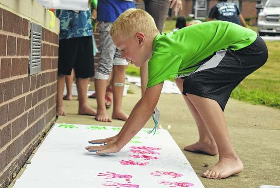 Quinn Darr, 6, leaves his handprints and footprints in paint on a piece of paper Wednesday during the Maker Fun Factor VBS: Created by God, Built for a Purpose at the First Baptist Church. Photo: Samantha McDaniel-Ogletree | Journal-Courier