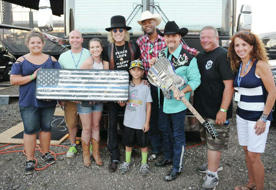 """Big Kenny"" Alphin (left center) and John Rich (holding guitar) of country music duo Big & Rich, along with fellow country musician ""Cowboy Troy"" Coleman (center), display the Fraternal Order of Police's End of Watch guitar and case during their appearance July 15 at the Morgan County Fair. The musicians signed the case ahead of the guitar and case being raffled off in August during the National FOP Conference in Nashville, Tenn. Chances to win the guitar are available for $25 at endofwatchguitar.com. Also pictured are Karlie Gusentine (from left), Illinois FOP Secretary Doug Thompson, Ashley Thompson, Talon Thompson, guitar developer and Williamson County FOP President Karl Gusentine and Heather Thompson. Photo: Photo Provided"