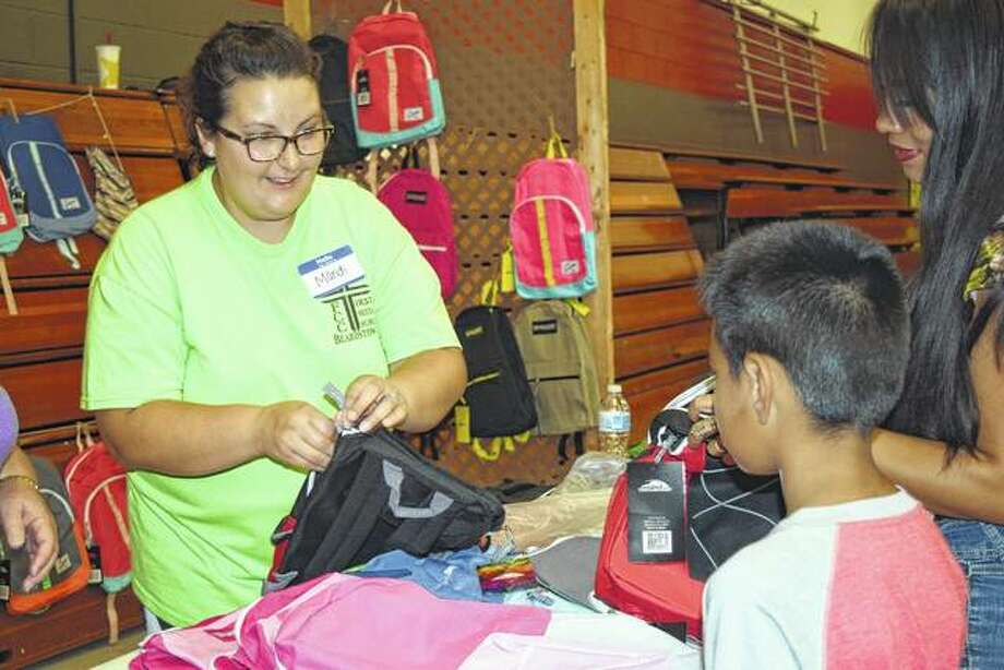 Volulnteer Mandi Ratay helps Daniel Barrera, 6, pick out a backpack with his mom, Belem Barrera, during the Back to School Fair Saturday at the First Christian Church in Beardstown. Photo: Nick Draper | Journal-Courier