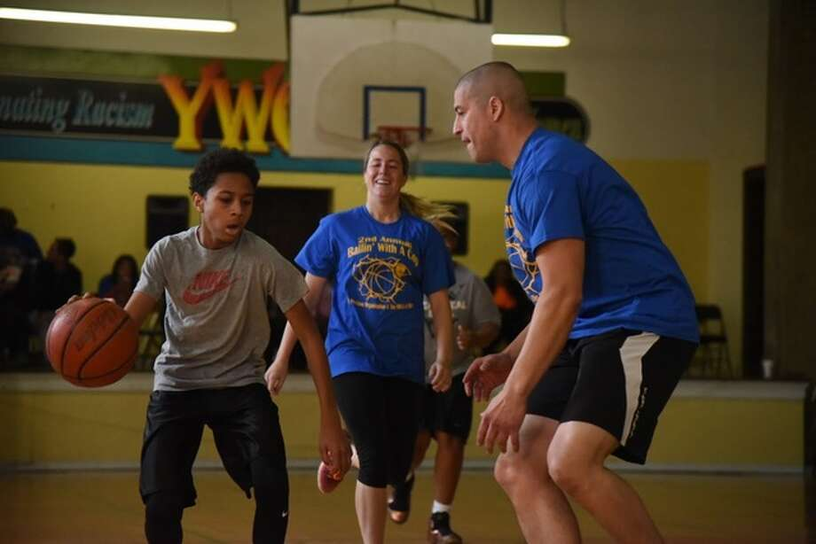 "Alton Det. Marcos Pulido, right, guards a young boy Saturday during the ""Ballin' with a Cop"" event."