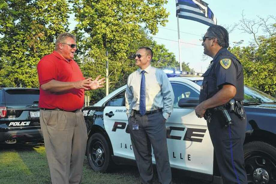 Jacksonville Mayor Andy Ezard (left) speaks with Jacksonville Police Chief Adam Mefford (center) and Tino Vasquez, a Jacksonville police patrolman, school resource officer and liaison with the Citizens Police Academy Alumni Association, Tuesday evening at the National Night Out event in Community Park.