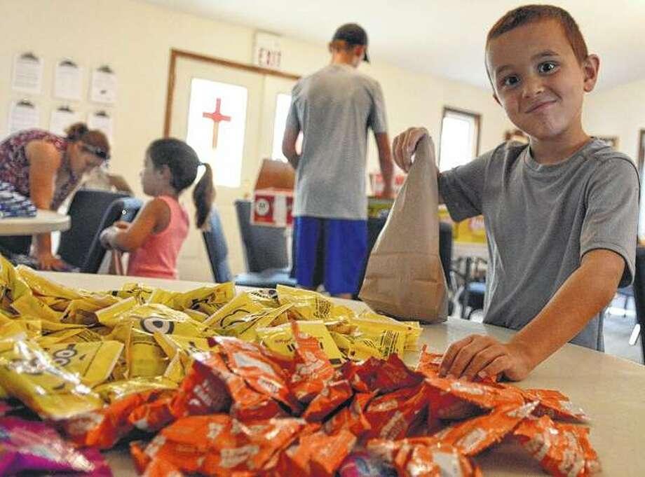 Garrett Turner of Modesto, a member of the Northwestern Green Machine's 4-H club, helps fill summer lunches. Photo: Kathleen Clark | Journal-Courier