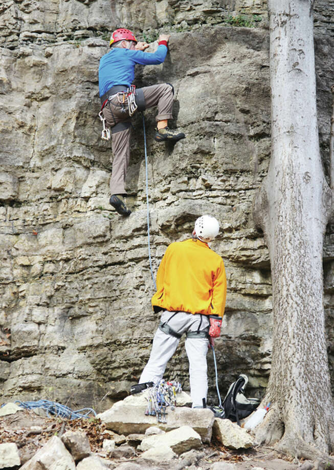 Two sport climbers take on one of the newly opened climbing routes at Pere Marquette State Park a few minutes after a ceremony formally opening the area Monday. When completed, the climbing area will offer 28 new routes on about eight rock faces.