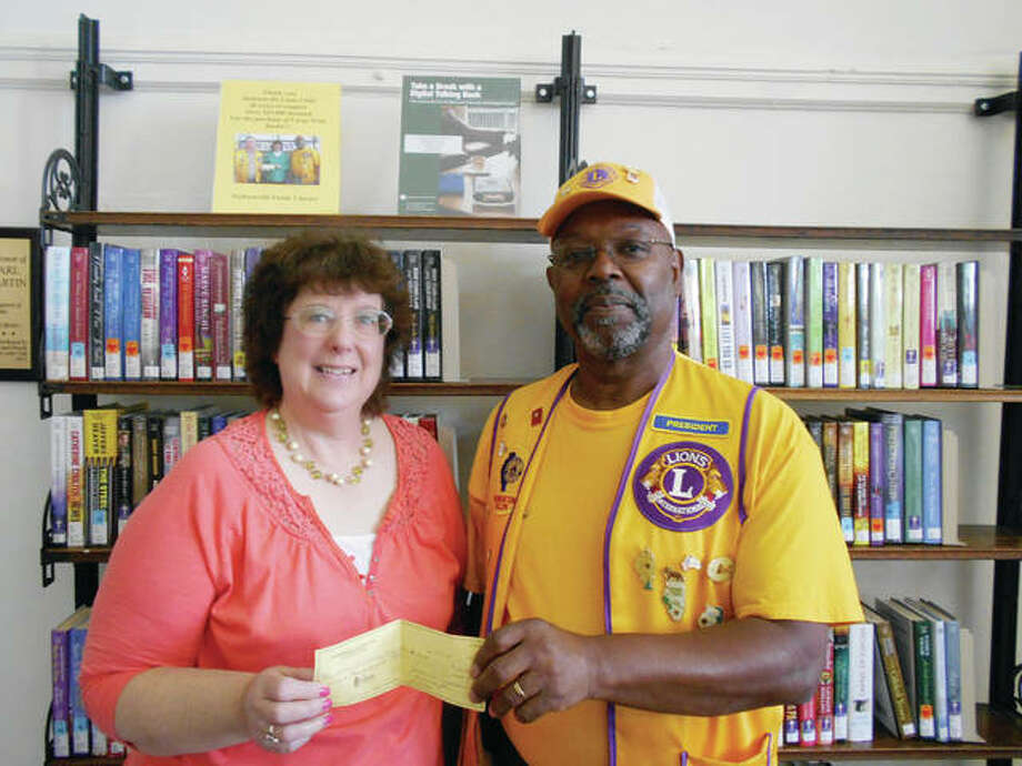 Aaron Singleton, president of the Jacksonville Lions Club, presents a check to Diane Hollendonner, outreach librarian for the Jacksonville Public Library, representing a donation of proceeds from the club's annual fruit sale. Since 1976, the club has donated a portion of its fruit sale proceeds to the library for the purchase of large-print books. Photo: Photo Provided