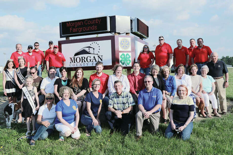 Jacksonville Rotary Club and Morgan County Fair Board members recently met at the fairgrounds to dedicate a new Morgan County Fair sign at South Westgate and West Lafayette avenues. The sign features two lighted, programmable LED message boards angled so one board is visible from each of the avenues. It represents Phase 1 of Rotary's Centennial Project, celebrating the club's 100th anniversary in 2018, to benefit the fairgrounds. On hand for the dedication were Little Miss Morgan County Olivia Haverfield (front, from left), Linda Grojean, Sandy Sanders, Lori Hartz, Craig Albers, Todd Evans, Lynne Sheaff, Junior Miss Morgan County Fair Queen Kaylee Ford (middle, from left), Miss Morgan County Fair Queen Taylor Zoerner, ToddCody, Steve Varble, Lisa Kluge, Brittany Henry, Cameron Jones, Nancy Thorsen (president, Jacksonville Rotary Club), Jon Valuck, Susan King, Daphne Spradlin, Tammy Middleton, Ginny Fanning, Phyllis Lape, Keith Lape, Mark Fromme (back, from left), Justin Becker, Seth Hetelle, Tim Degroot, Jay Harris, Cheri Orris, Larry Robinson, Andy White, Bryan Richardson and Mark Stiltz. Photo: Photo Provided