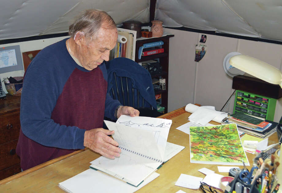 Gene Ursprung flips through one of his sketchbooks in his art studio. Photo: Vicki Bennington/For The Telegraph
