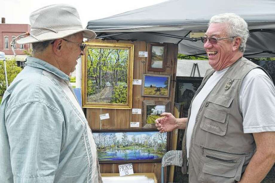 Dave Tannahill of Franklin (left) talks with Tom Atkins of Jacksonville on Saturday at Atkins' display of acrylic paintings at Jacksonville Main Street's Craft Brew Festival & Artisan Fair in Central Park. Photo: Greg Olson | Journal-Courier
