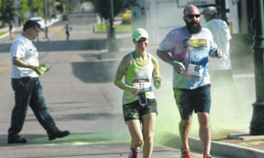 Jodie Reed and Scott Reed run through a cloud of green at the finish line of Saturday's Colors United 5K Run/Walk in downtown Jacksonville. The event was a first for Prairieland United Way, and drew about 60-70 runners and walkers. (More photos at myjournalcourier.com).