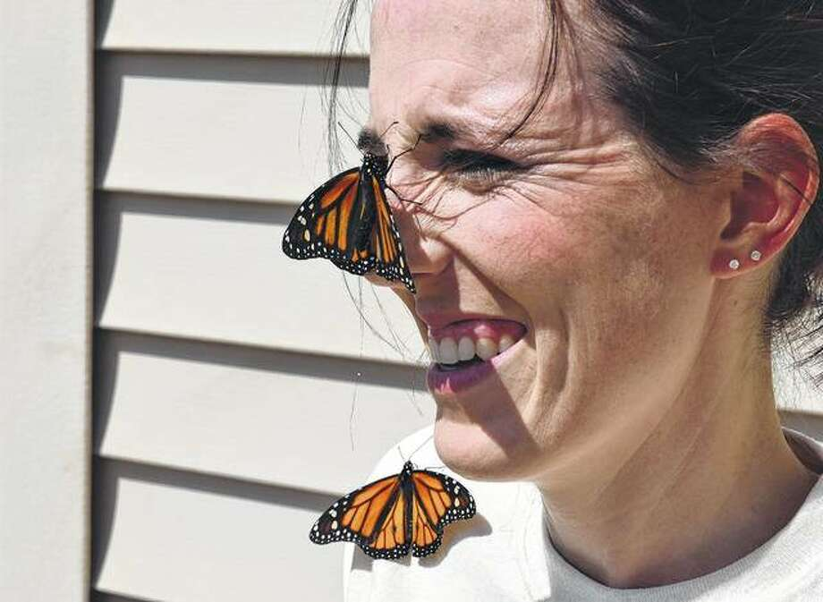 Hannah Lovekamp of Beardstown, a teacher at Gard Elementary School in Beardstown, has monarch butterflies land on her nose and shoulder during a two-day teacher workshop at the University of Illinois Extension Office in Jacksonville.